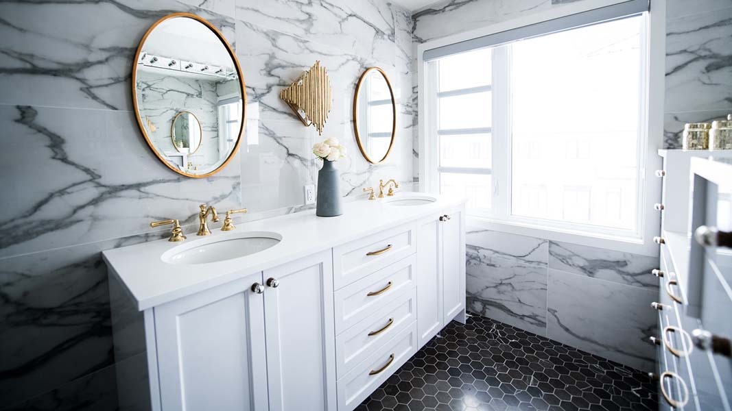 luxury bathroom with marble white tiles and white vanity, gold framed round mirrors on the wall